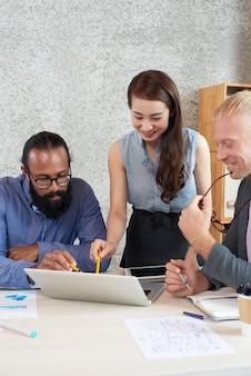 オフィスでの作業会議でノートパソコンの画面を見ている同僚の多国籍グループ