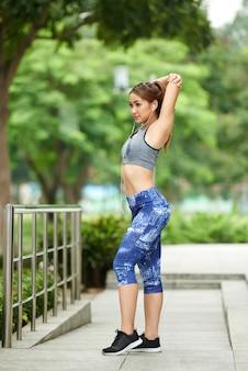 スポーツトップと公園で腕のストレッチをしているレギンスの若いアジア女性