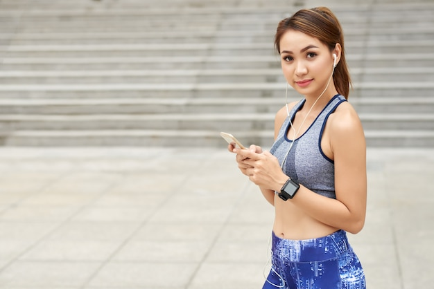 イヤホンと通りでポーズをとってスマートフォンで、スポーツウェアでアジアの女性に合う