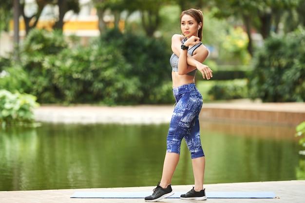 都市公園の池のそばに立って、腕のストレッチを行う運動のアジア女性