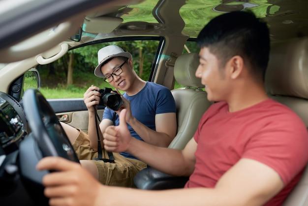 ステアリングホイールの後ろに車に座って、カメラで友人のためにポーズアジア人