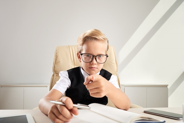 オフィスの机に座って、カメラに向かって指しているメガネの金髪白人少年
