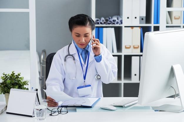 Азиатский женский доктор сидя на столе в офисе и вызывая на мобильном телефоне