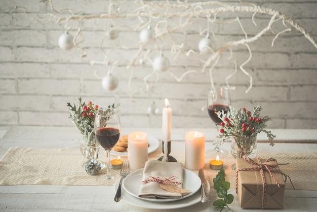 Подарок, тарелки, столовые приборы, свечи и украшения на столе к рождественскому ужину