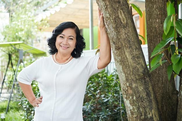 Старшая азиатская женщина представляя в саде и полагаясь на дереве