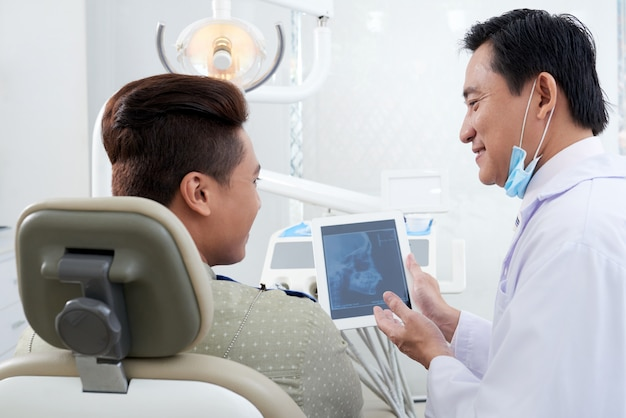 Азиатский мужской стоматолог демонстрирует рентгеновское изображение челюсти на планшете для пациента