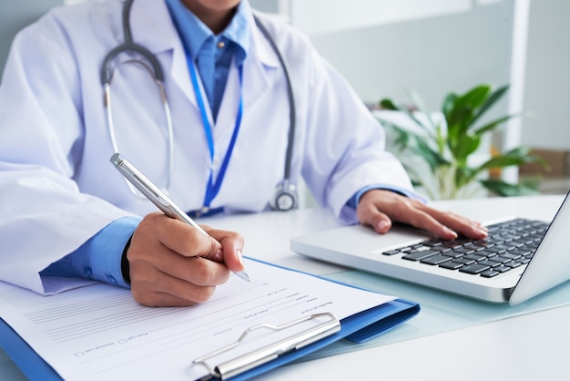 Руки до неузнаваемости женщина-врач писать на форме и печатать на клавиатуре ноутбука