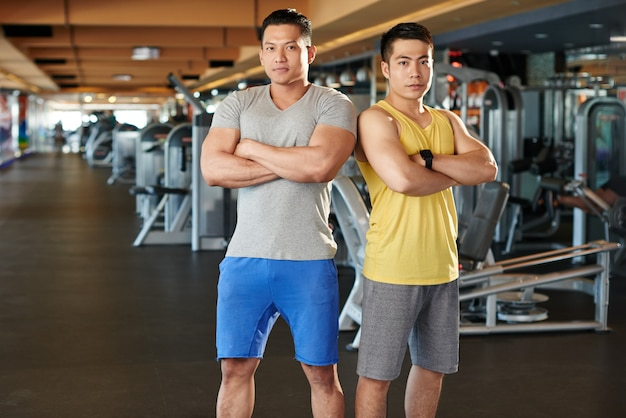 ジムで肩を並べて立っているボディービルダーが筋肉を披露