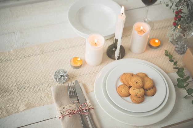 Тарелка печенья на столе, накрытый для рождественского ужина