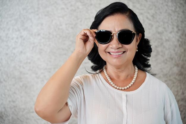 カメラに歯を見せる笑顔を与えるサングラスをかけているスタイリッシュなアジアの女性