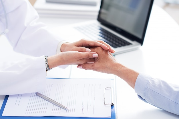 Обрезанные руки доктора успокаивают неузнаваемого пациента