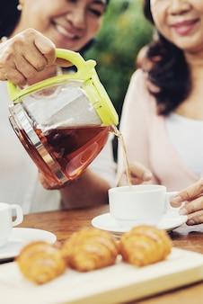 ティーポットからカップにお茶を注ぐ陽気なアジアの女性、およびテーブルにクロワッサン