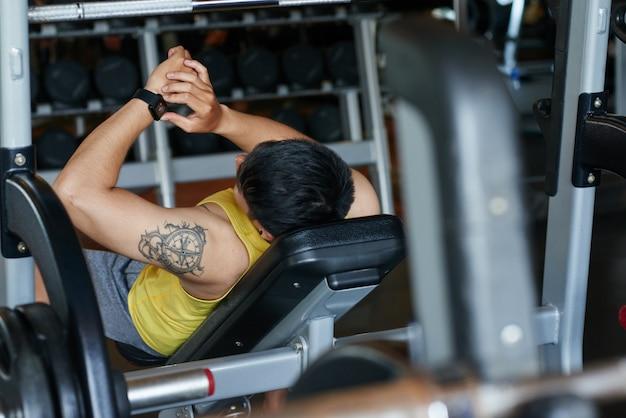 Татуированный мужчина лежал на скамейке в тренажерном зале и смотрит на умные часы
