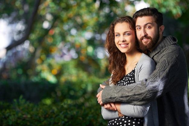 男が公園で彼のガールフレンドを抱いて