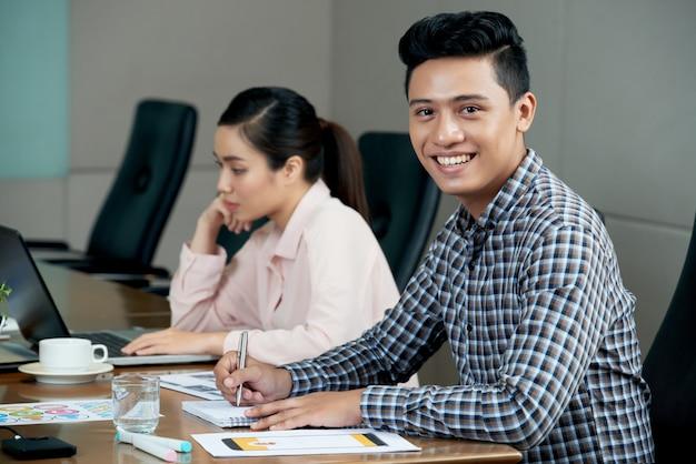 Молодой азиатский человек сидя на столе встречи в офисе и усмехаться, и женщина работая на компьтер-книжке
