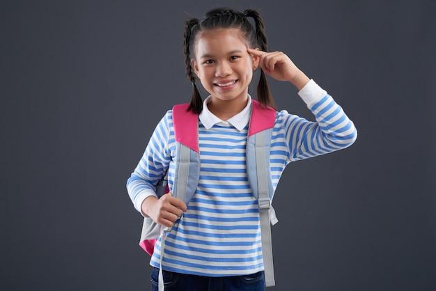 Азиатская школьница с рюкзаком позирует пальцами касаясь виска