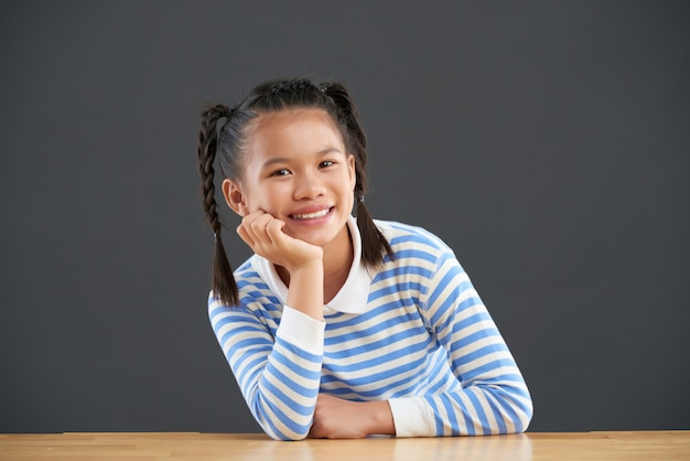 Счастливая азиатская девушка с оплетками сидит с подбородком на одной руке