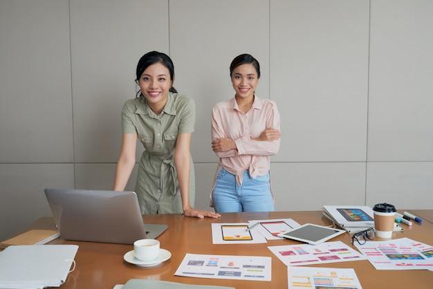 Две креативные азиатские женщины позируют в офисе, с ноутбуком, документами и фотографиями на столе