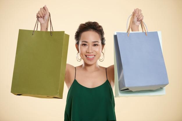 Молодая азиатская женщина представляя и задерживая хозяйственные сумки в каждой руке