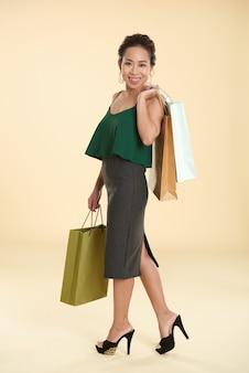 Шикарная молодая азиатская женщина представляя с хозяйственными сумками