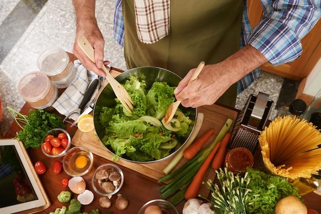 Вид сверху обрезанного человека в поварском фартуке, смешивающем салат