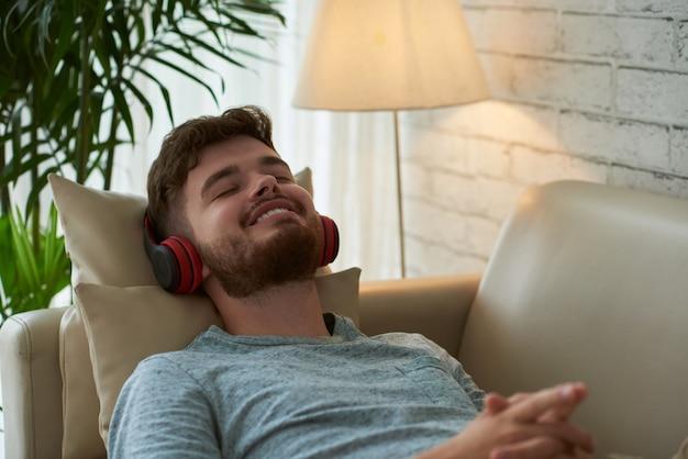 Макрофотография битник парень расслабляющий на своем диване, слушать музыку