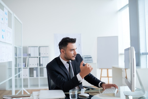 Молодой кавказский бизнесмен в костюме сидя в офисе и смотря экран компьютера