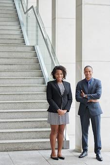 Веселый афроамериканский мужчина и женщина, стоя в офисе в нижней части лестницы