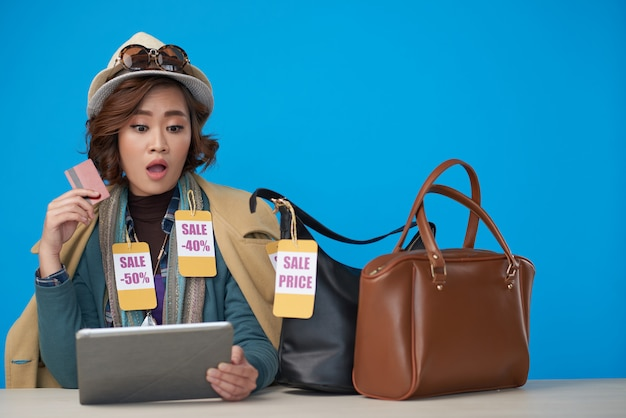 Азиатская женщина, одетая в новую одежду со скидкой этикетки, сидя с планшета и кредитной карты