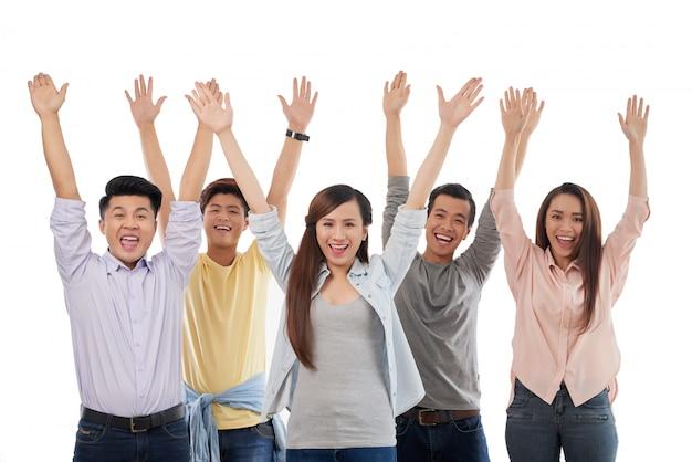 Группа возбужденных небрежно одетых мужчин и женщин, позирует с поднятыми руками