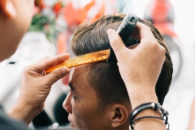 Неузнаваемый мужской парикмахер стрижет волосы клиента триммером и расческой