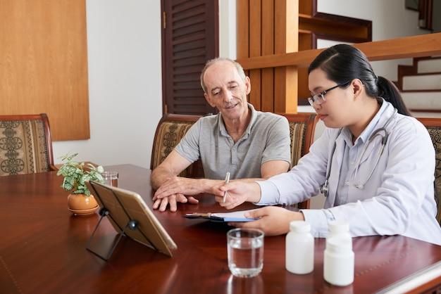 家の呼び出し中に上級白人患者に話しているアジアの女性医師