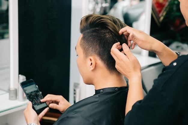 クライアントの髪にワックスを適用する認識できないトリミングされた美容師の肩越しに