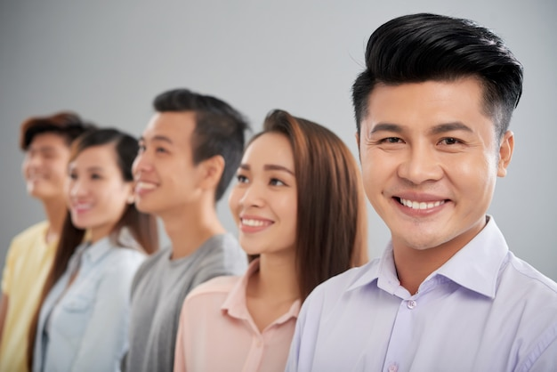 Счастливый азиатский человек смотря камеру стоя на переднем плане его коллег