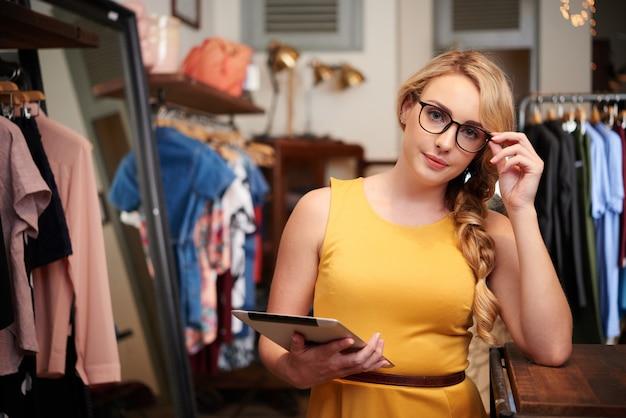 Портрет молодой блондин продавца, стоя в магазине одежды с цифровой планшет