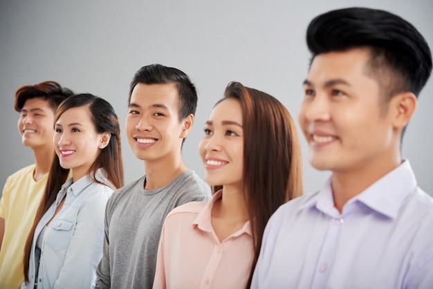 Вид сбоку людей, стоящих в ряд и улыбающихся