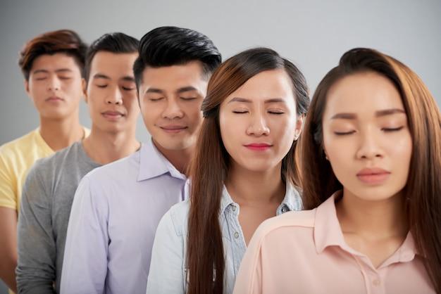 Группа азиатских мужчин и женщин, стоящих в ряду с закрытыми глазами