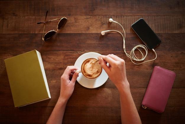 メガネ、本、財布、テーブルの上に横たわるスマートフォンでカプチーノをかき混ぜるトリミングされた手の平面図