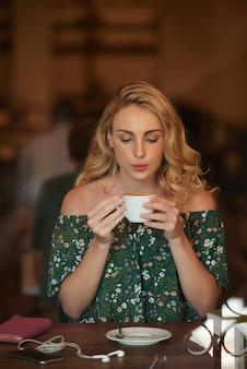 Портрет довольно блондинка сидит за столом кафе и пьет кофе