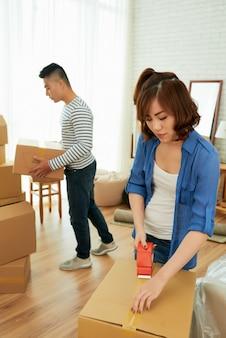 Женщина упаковывает коробки с мужем, несущим пакеты