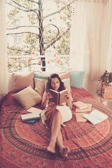 彼女のベッドで横になっている本を読んでいる女性の完全なショット
