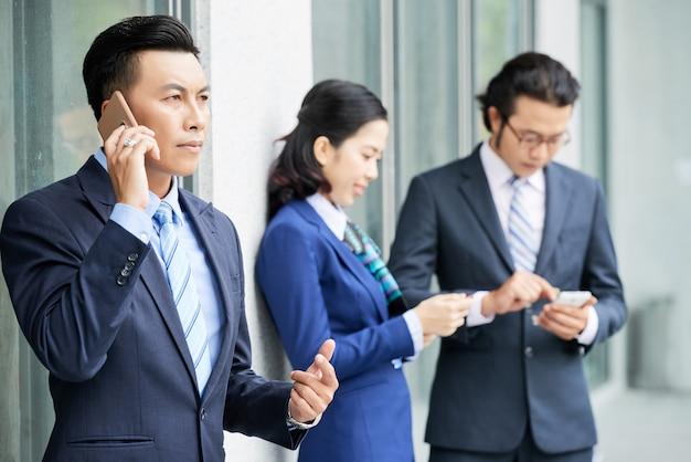屋外のスマートフォンを持つ若いビジネス人々