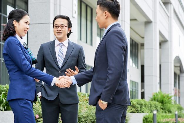 屋外握手するビジネス人々のミディアムショット