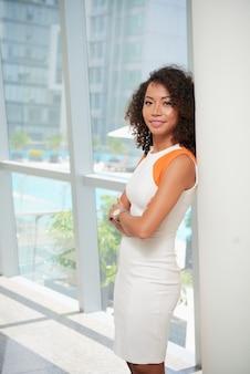 アジアの女性がオフィスの窓でポーズのミディアムショット