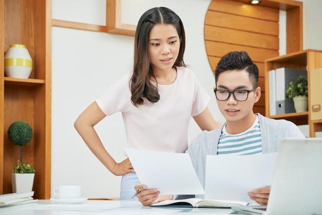 Азиатские коллеги работают с бумагами в офисе