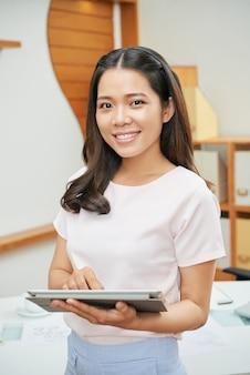Довольно азиатская женщина с таблеткой в офисе