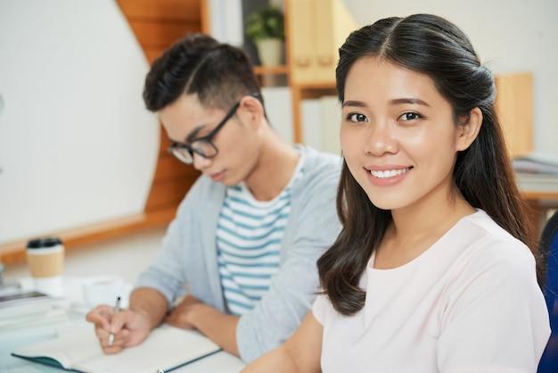 Улыбаясь азиатская женщина с коллегой-мужчиной за столом