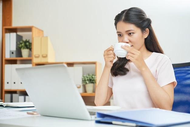 現代の女性がオフィスでコーヒーを飲む