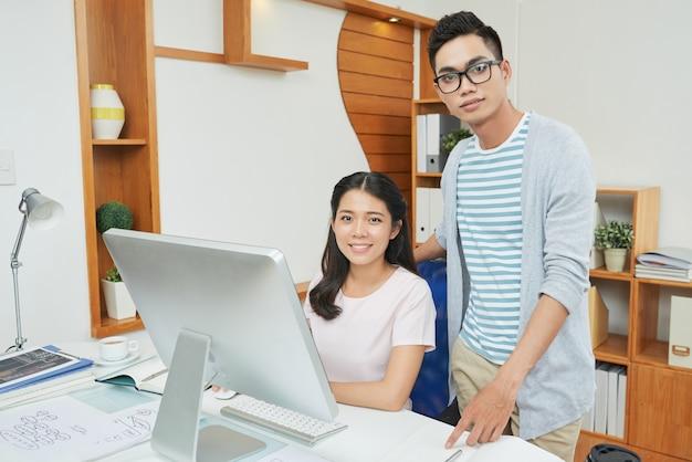 Уверенные молодые профессиональные работники в офисе