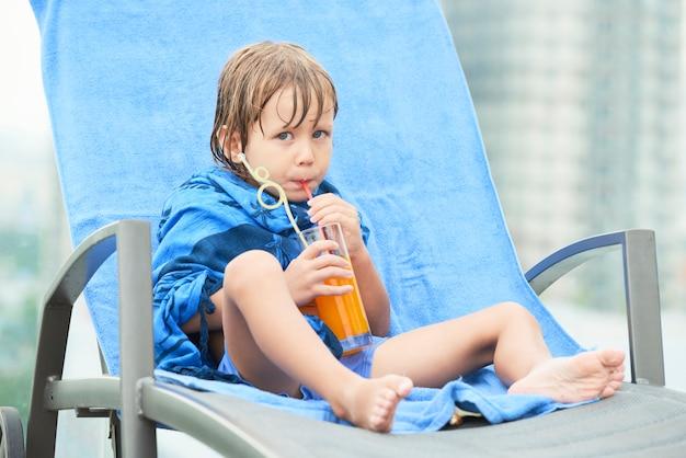 水泳の後のジュースを飲む子供